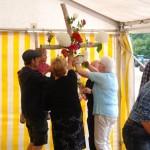 Das schmücken des Kreuzes mit Blumen vor dem Gottesdienst